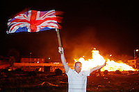 A man waves the British flag in celebration as the Irish flag is burned on giant bonfires made from pallets and old tyres on a Loyalist estate, Belfast Northern Ireland. on July 11, 2008.The bonfires which are seen by the Protestant community as a celebration of loyalist culture in the province are lit on the eve of 12 July, which is the anniversary of the Battle of the Boyne at which the Protestant King William of Orange defeated the Catholic King James in 1690.