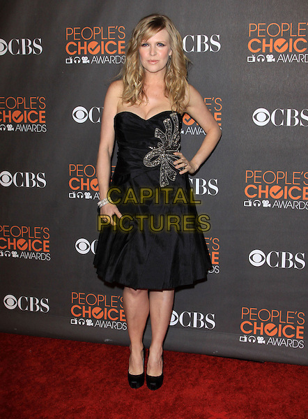 ASHLEY JENSEN.Arrivals at the 2010 People's Choice Awards held at the Nokia Theater L.A. Live in Los Angeles, California, USA. .January 6th, 2010 .full length black strapless dress hand on hip gold bow ribbon shoes clutch bag .CAP/ADM/KB.©Kevan Brooks/AdMedia/Capital Pictures.