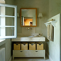 A simple storage unit with individual baskets beneath a stone wash basin is painted to match the walls of this bathroom