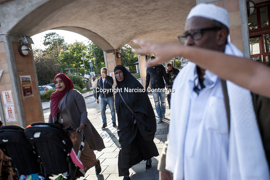 """August 29, 2018: MOHAMMED HADJI FARAH, a 65 years-old immigrant form Somalia (right front), speaks out to the media in the Rinkeby neighborhood. Rinkeby area, known for its large population of immigrants, was labeled unofficially as a """"no-go zone"""" due its high rate in felony crime activity."""