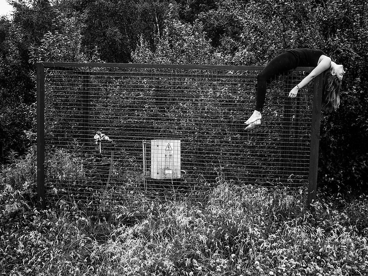Daylight shot of a girl hanging awkwardly on top of a fence in a land fill site in Yorkshire England.