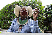 9 June 2014. Kayapo Chief Raoni Metuktire during his visit to London. The chief sits smoking his pipe.