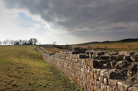 Section of Hadrian's Wall rebuilt in stone from Birdoswald Roman Fort to Harrow's Scar, Cumbria, England. Hadrian's Wall was built 73 miles across Britannia, now England, 122-128 AD, under the reign of Emperor Hadrian, ruled 117-138, to mark the Northern extent of the Roman Empire and guard against barbarian attacks from the Picts to the North. The wall was fortified with milecastles with 2 turrets in between, and a fort about every 5 Roman miles. This section of the Wall is managed by English Heritage, and the Hadrian's Wall Path, an 84-mile coast to coast long distance footpath, runs alongside it. Picture by Manuel Cohen