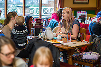A mother sitting at a table talks to a friend as she breastfeeds her two year old daughter in the family restaurant and play area of a pub.<br /> <br /> Lancashire, England, UK<br /> <br /> Date Taken:<br /> 07-01-2015<br /> <br /> &copy; Paul Carter / wdiip.co.uk