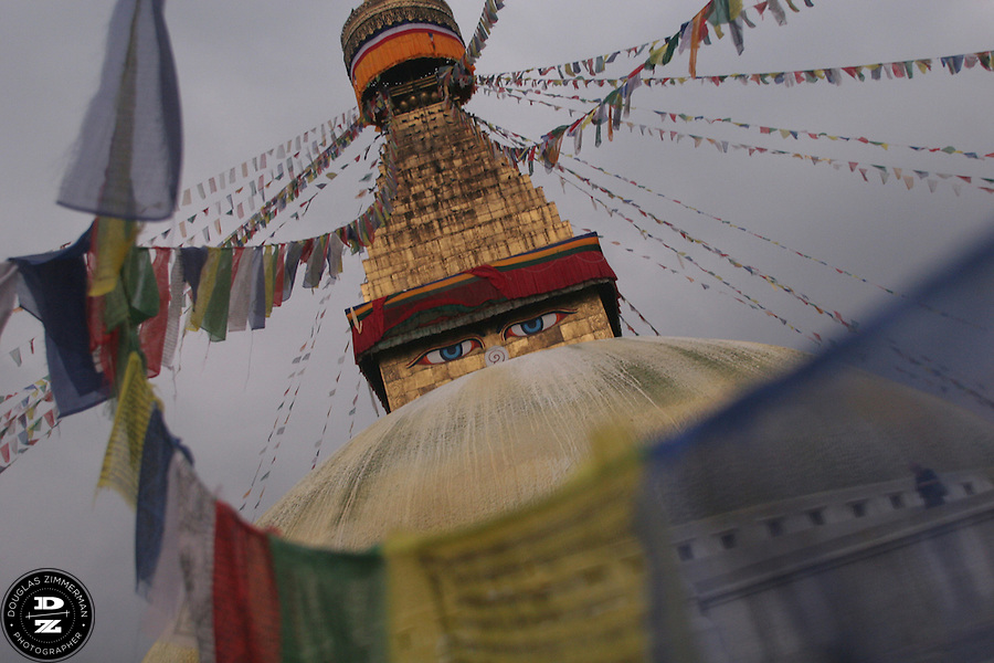 Prayer flags blow in the wind as they hang from the stupa at Boudha (or Boudhanath) just outside Kathmandu, Nepal.  The stupa is considered  the most important Tibetan Buddhist monument outside Tibet.  Photograph by Douglas ZImmerman