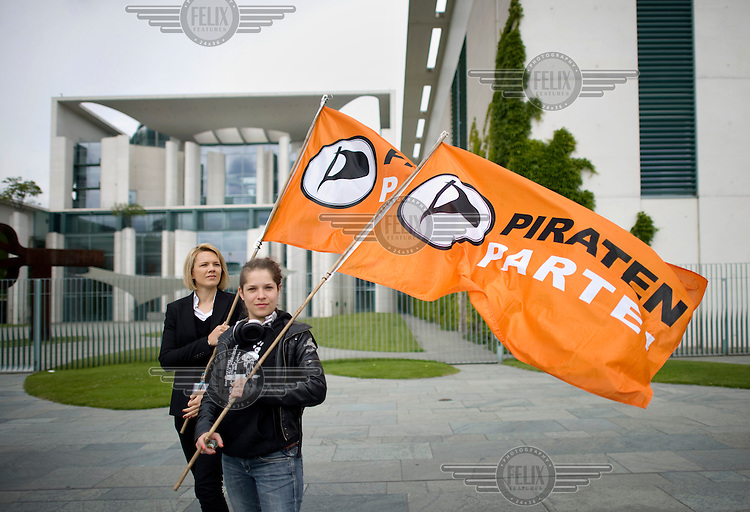 Protesters demonstrate with the flag of the Piratenpartei, the Pirate Party 'Die Piraten', in front of the German federal chancellory against a government child-care subsidy.