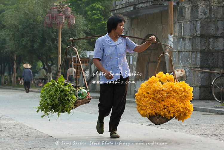 Woman carrying a very heavy load of pumpkin flowers, which are sold for sauces, at a village market in Yangshuo, Guangxi, China.