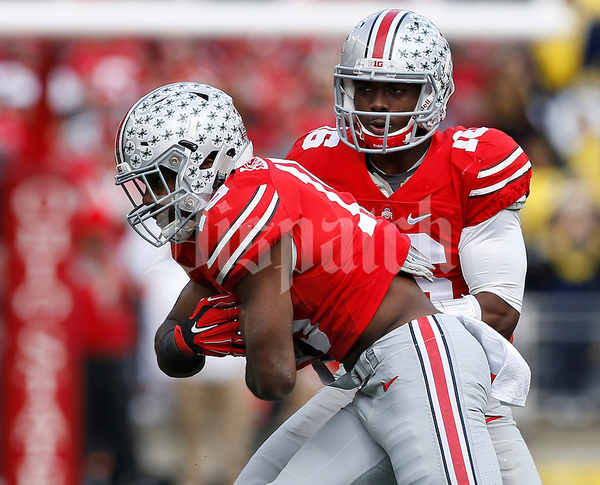 Ohio State Buckeyes quarterback J.T. Barrett (16) hands off to running back Ezekiel Elliott (15) during the first quarter of the NCAA football game at Ohio Stadium on Nov. 29, 2014. The Buckeyes won 42-28. (Adam Cairns / The Columbus Dispatch)