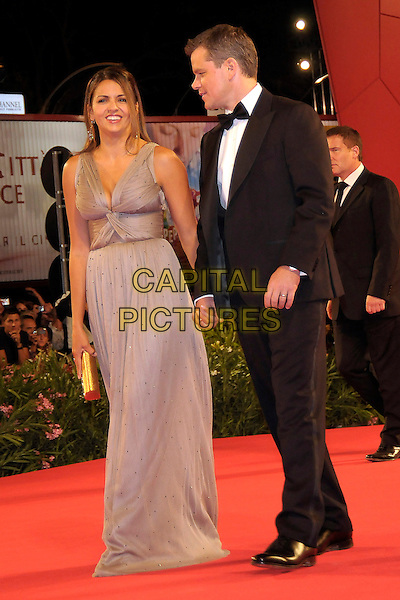 "LUCIANA BARROSO & MATT DAMON.Arrive for the premiere of ""The Informant"" at the Palazzo del Casino during 66th Venice International Film Festival, Lido, Venice, Italy, 7th September 2009..full length married couple husband wife brown grey gray dress long maxi black tux tuxedo black bow tie holding hands clutch bag gold .CAP/RD.©Richard Dean/Capital Pictures."