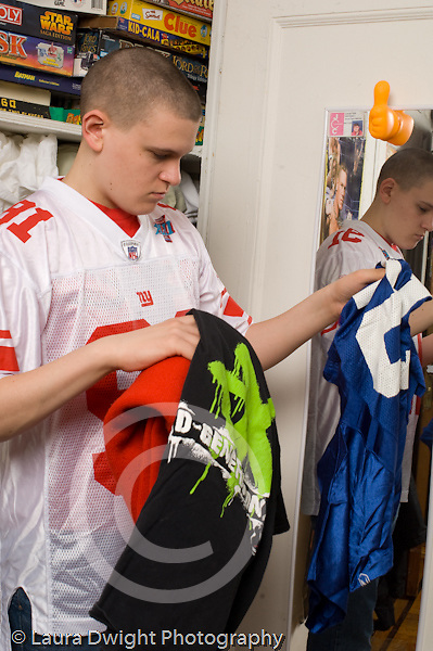 Teenage boy age 17 looking at clothes near bedroom closet trying to decide what to wear white caucasian