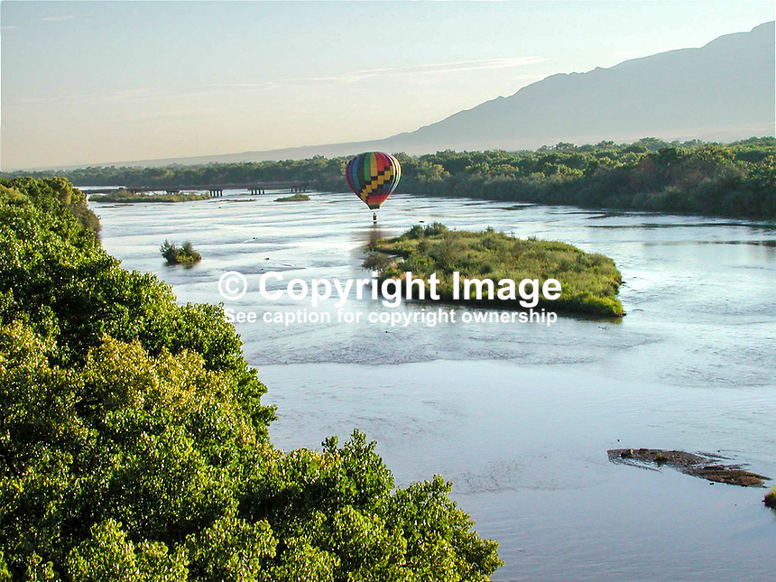 Hot air balloon floats over the Rio Grande. Cottonwood trees line the river for most of its journey through New Mexico. This section of the river is near Albuquerque. 2000091051..Copyright Image from Victor Patterson, 54 Dorchester Park, Belfast, UK, BT9 6RJ..Tel: +44 28 9066 1296.Mob: +44 7802 353836.Voicemail +44 20 8816 7153.Skype: victorpattersonbelfast.Email: victorpatterson@mac.com.Email: victorpatterson@ireland.com (back-up)..IMPORTANT: If you wish to use this image or any other of my images please go to www.victorpatterson.com and click on the Terms & Conditions. Then contact me by email or phone with the reference number(s) of the image(s) concerned.