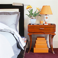 A stack of Hermes boxes that once contained the bed linen is stored beneath a 1930s side table in the contemporary bedroom