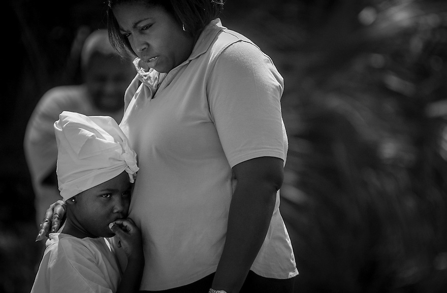 A member of the Mt. Calvary Missionary Baptist Church comforts her daughter before she is baptized watches in a traditional Gullah Geechee river baptism ceremony.