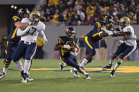 WVU running back Dustin Garrison runs through a big hole. The WVU Mountaineers beat the Pitt Panthers 21-20 at Mountaineer Field in Morgantown, West Virginia on November 25, 2011.