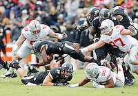 Purdue Boilermakers running back Raheem Mostert (8) falls over teammate Purdue Boilermakers tight end Justin Sinz (84) as he gets gets tripped up by Ohio State Buckeyes linebacker Camren Williams (55), defensive lineman Joey Bosa (97) and defensive tackle Joel Hale (51) during the third quarter of the NCAA football game at Ross-Ade Stadium in West Lafayette, Ind. on Nov. 2, 2013. (Adam Cairns / The Columbus Dispatch)