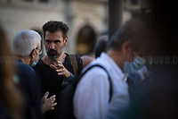 """Fabrizio Gifuni (Actor). <br /> <br /> Rome, 27/07/2020. Today, hundreds of people, NGO's (ONG) representatives, actors and politicians gathered in Piazza San Silvestro (near the Italian Parliament) to protest (1.) against the dramatic situation in Libya - erupted in a civil war between the GNA (2.) and the forces of General Khalifa Belqasim Haftar - and to protest against the inhumane conditions of migrant people trapped in legal and illegal prisons in Libya. The aim of the demo was to call the Italian Government to stop funding the """"Libyan Coast Guard"""" and to immediately help and free People in Libya throughout """"Humanitarian Corridors"""", and give them the protection they are entitled of by the International Human Rights Conventions. <br /> From the organisers Facebook event page: «[…] we meet to ask the Italian Government and the European States to stop funding the so-called Libyan coast guard, to close and evacuate the detention centres by transferring migrants out of Libya and to promote corridors to help people on the run find protection without endangering their lives. The men, women and children who take the sea from the Libyan coast flee from situations of extreme misery, despotic regimes, tribal persecutions, ethnic conflicts, wars and environmental catastrophes. And in Libya they are subjected to violence, extortion, detention, torture, rape and torture. A few days ago, on July 16, the Chamber of Deputies [Of the Italian Parliament, ndr] for the fourth consecutive year approved the financing of the Italian mission in Libya, which provides financial support for the so-called Libyan coastguard and training and training of its members. […] The mobilization will be accompanied by readings by Ascanio Celestini, Valentina Carnelutti, Fabrizio Gifuni and Sonia Bergamasco […]».<br /> <br /> Footnotes & Links:<br /> 1. https://www.facebook.com/events/2732849460337428/<br /> 2. 07.05.19 Prime Minister of Libya Fayez al-Serraj Met Italian PM Giuseppe Conte at Palazzo """