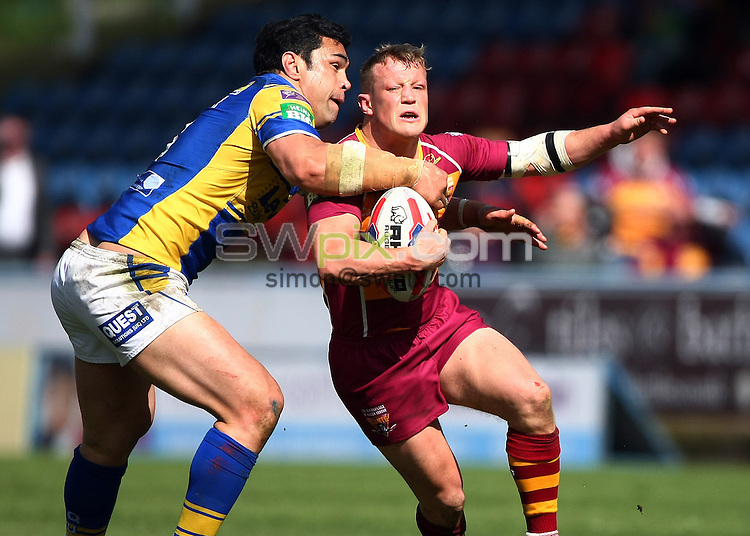 PICTURE BY VAUGHN RIDLEY/SWPIX.COM - Rugby League - Tetley's Challenge Cup, 5th Round - Huddersfield Giants v Leeds Rhinos - John Smiths Stadium, Huddersfield, England - 11/05/13 - Huddersfield's Luke Robinson is tackled by Leeds Kylie Leuluai.