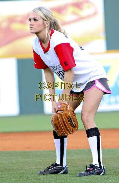 CARRIE UNDERWOOD.10th Annual City of Hope Celebrity Softball Tournament between the Grand Ol' Opry and Blair Garner's After Midnight teams at Greer Stadium, Nashville, TN, USA, June 7th, 2010..full length playing game sports sport glove red and white t-shirt shorts socks side profile .CAP/ADM/DH.©Dan Harr/AdMedia/Capital Pictures.