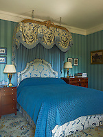 An antique canopy has been added to a modern bed embellished with blue and gold fabric to create an elegant guest bedroom