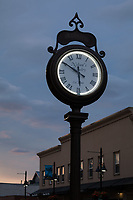 Large antique clock at dusk, Auburn, Washington State, USA.