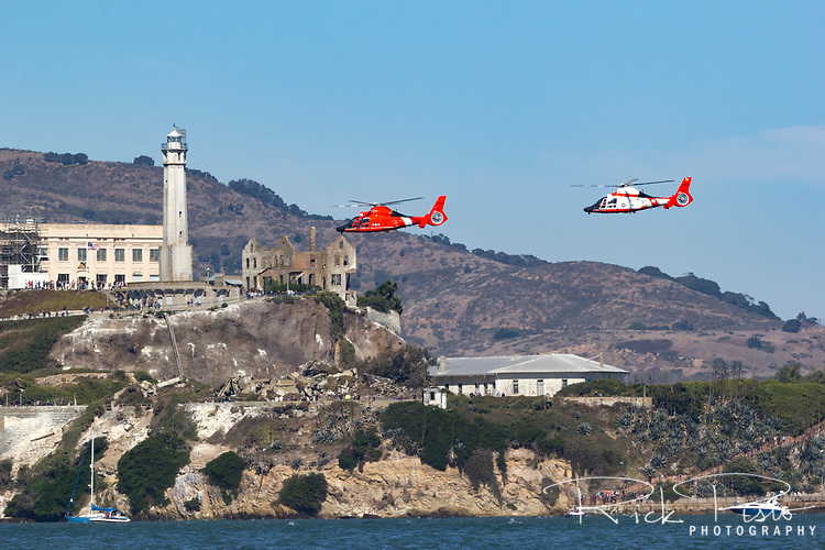 A pair of Coast Guard MH-65 Dolphin helicopters from Air Station San Francisco fly near Alcatraz on San Francisco Bay.