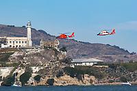 A pair of Coast Guard MH-65 Dolphin helicopters from Air Station San Francisco fly near Alcatraz on San Francisco Bay.