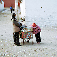 A Hui (muslim) woman is waiting for customers with her daughter  in front of the Main Assembly Hall in the buddhist  monastery of Labrang, the first day of the Great Prayer(Monlam Chenmo). Xiahe, China.