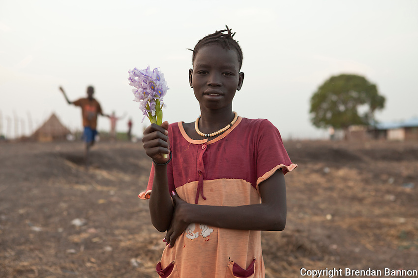 Portrait of a girl holding flowers in Nasir, South Sudan.