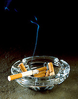 STILL LIFE: NEGATIVE IMAGE OF CIGARETTES<br /> In Full Ashtray<br /> Hot gases from a lit cigarette (made visible by smoke particles) first move  in a streamline or laminar flow and then in a turbulent flow.