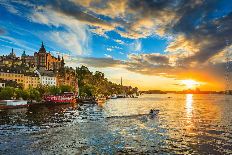 Mariaberget och en motorbåt på Riddarfjärden i solnedgång i Stockholm