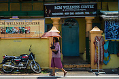 A pedestrian walks past an Ayurvedic centre in Kochi, Kerala, India.