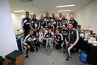 Pictured: Team staff with the cup in the changing rooms. Sunday 24 February 2013<br /> Re: Capital One Cup football final, Swansea v Bradford at the Wembley Stadium in London.