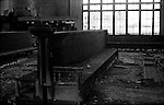 Wooden benches collecting dust in an abandoned railroad station's waiting room, speak of a by-gone era.