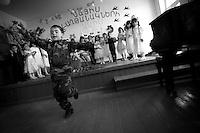 """Nagorny-Karabach, 12.05.2011, Shushi. Ein Junge in Tarnfleck-Uniform tanzt vor den Eltern der Grundschulkinder und Offiziellen zu Ehren der Soldaten des Karabach-Krieges. """"The Twentieth Spring"""" - ein Portrait der s¸dkaukasischen Stadt Schuschi, 20 Jahre nach der Eroberung der Stadt durch armenische K?mpfer 1992 im B¸gerkrieg um die Unabh?ngigkeit Nagorny-Karabachs (1991-1994). A little boy dressed in camouflage performs for pupils parents and officials to celebrate Shushis liberation in a primary school. """"The Twentieth Spring"""" - A portrait of Shushi, a south caucasian town 20 years after its """"Liberation"""" by armenian fighters during the civil war for independence of Nagorny-Karabakh (1991-1994). .Un petit garçon habillé en tenue de camouflage défile pour les parents d'élèves et des fonctionnaires pour célébrer la libération de Shushis, dans une école primaire.""""Le Vingtieme Anniversaire"""" - Un portrait de Chouchi, une ville du Caucase du Sud 20 ans après sa «libération» par les combattants arméniens pendant la guerre civile pour l'indépendance du Haut-Karabakh (1991-1994)..© Timo Vogt/Est&Ost, NO MODEL RELEASE !!"""