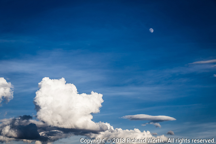A gibbous moon looks down on sculpted clouds floating in a blue western Colorado sky.