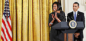 United States first lady Michelle Obama (L) speaks as U.S. President Barack Obama (R) looks on during a reception in honor of International Women's Day at the East Room of the White House Monday, March 8, 2010 in Washington, DC. The reception honored women from around the world and their achievements. .Credit: Alex Wong - Pool via CNP