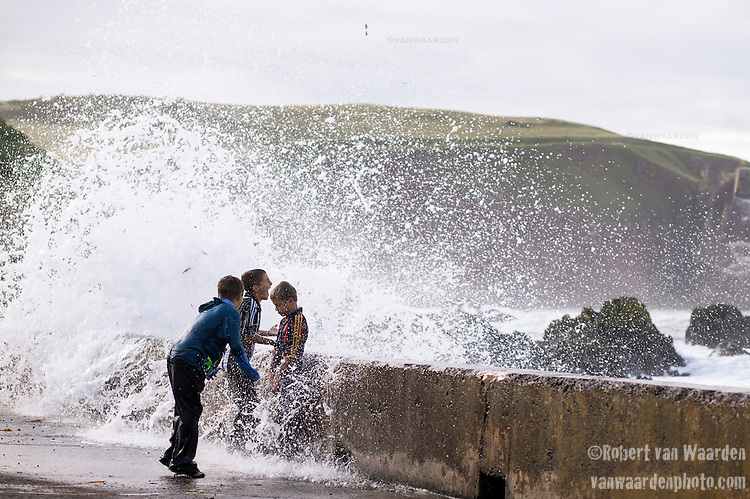 Boys play in the waves that crash over the breakwater in village of St. Abbs in North East England.