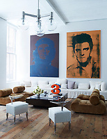 A pair of paintings by Gavin Turk hangs above an Axel Vervoordt sofa in the library; the 1970s suede chairs are by Klaus Uredat, a Robert Indiana sculpture sits atop a vintage French cocktail table, and the 1960s chandelier is Austrian; The Philippe Starck chairs in the library were prototypes for the Royalton Hotel. The 18th-century floorboards were salvaged from a Pennsylvania farmhouse.