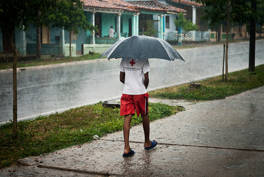 A young cuban walking under the rain on the main street of Viñales with a t-shirt from the american red cross.