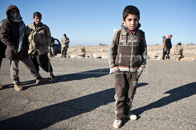 11/12/2014. Sinjar Mountain, Iraq. A young Yazidi refugee is pictured on a road on Mount Sinjar as he waits for possible evacuation by Iraqi Air Force Helicopters. <br /> <br /> Although a well publicised exodus of Yazidi refugees took place from Mount Sinjar in August 2014 many still remain on top of the 75 km long ridge-line, with estimates varying from 2000-8000 people, after a corridor kept open by Syrian-Kurdish YPG fighters collapsed during an Islamic State offensive. The mountain is now surrounded on all sides with winter closing in, the only chance of escape or supply being by Iraqi Air Force helicopters.