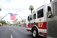 Phoenix, Arizona. July 7, 2013 - Nineteen hearses for each of the fallen members of the Granite Mountain Hotshots Arizona firefighting crew who died last week formed a procession to honor them in Phoenix as their bodies were taken back home to Prescott, about an 80-mile route. An engine from the Phoenix Fire Department makes its way toward the site where people and firefighters from all over the state gathered to see the procession. Photo by Eduardo Barraza © 2013