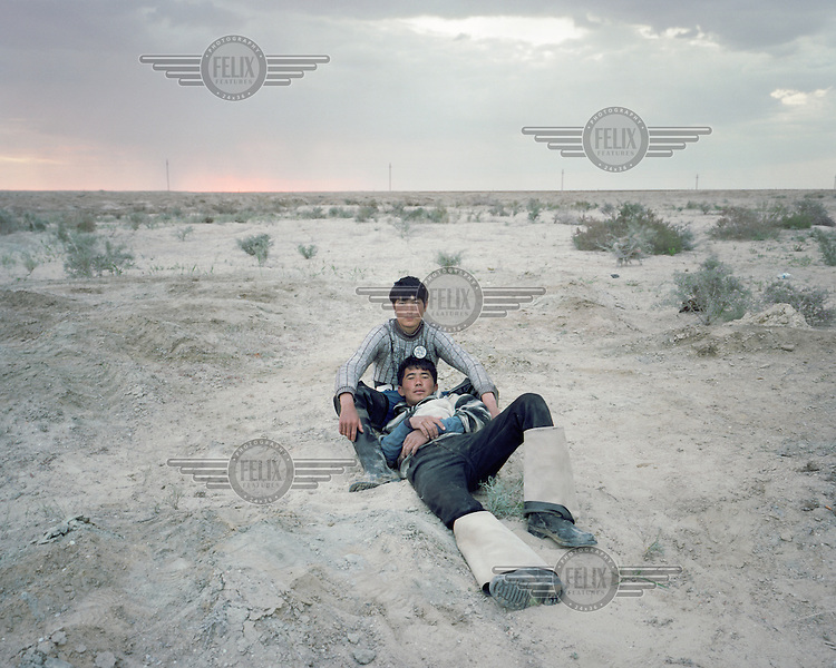 Two young fishermen lie in the desert as dawn breaks. A whole generation were rendered jobless with the collapse of the fishing industry in the Aral Sea. Now, though opportunities are limited, and pay is meagre, they are again able to do what their fathers did.