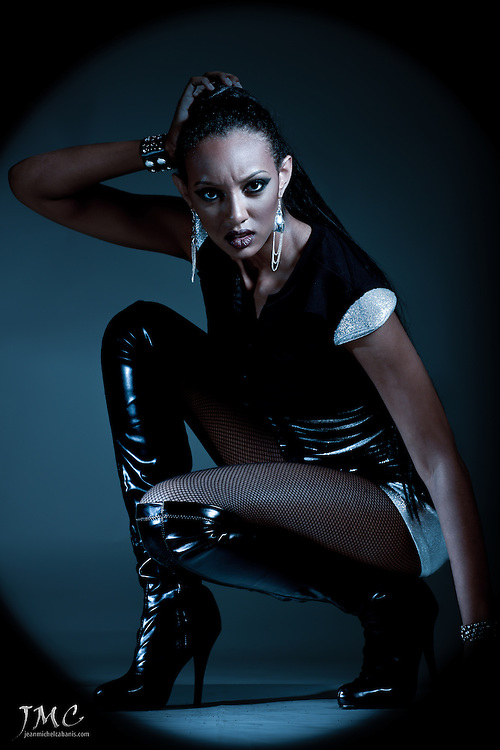 Stunning fashion model, kneeling in black boots, in blue light, closeup