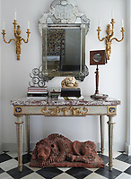 A collection of objects is artfully displayed on a gilded console table with a marble top. Two gilt sconces and a Venetian mirror complete the arrangement.