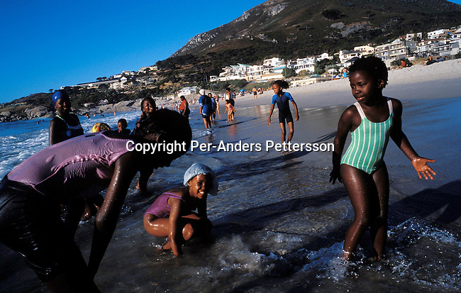 CAMPS BAY, SOUTH AFRICA - JANUARY 1: Children play in the water as the sun sets on January 1, 2003 in Camps Bay outside Cape Town, South Africa. Camps Bay has some of the best beaches and most expensive properties in the country, and it?s a popular place for locals and foreign visitors. .(Photo: Per-Anders Pettersson/Getty Images)........