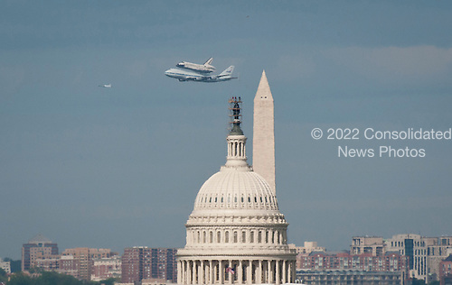 Space shuttle Discovery, mounted atop a NASA 747 Shuttle Carrier Aircraft (SCA) flies near the U.S. Capitol, Tuesday, April 17, 2012, in Washington. Discovery, the first orbiter retired from NASAs shuttle fleet, completed 39 missions, spent 365 days in space, orbited the Earth 5,830 times, and traveled 148,221,675 miles. NASA will transfer Discovery to the National Air and Space Museum to begin its new mission to commemorate past achievements in space and to educate and inspire future generations of explorers..Mandatory Credit: Rebecca Roth / NASA via CNP