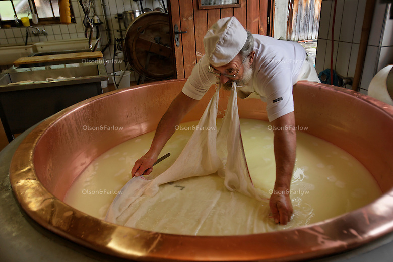 Alfons Bour makes alpkese cheese by warming the milk with a wood stove and gathering it with cheese cloth to put into molds.  Then it is put into a cooler and it is aged.  He also makes butter on a farm in Switzerland.