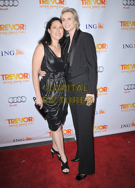 Dr. Lara Embry and Jane Lynch.Trevor Live at The Hollywood Palladium in Hollywood, California, USA..December 4th, 2011  .full length dress   black suit couple clutch bag.CAP/RKE/DVS.©DVS/RockinExposures/Capital Pictures.