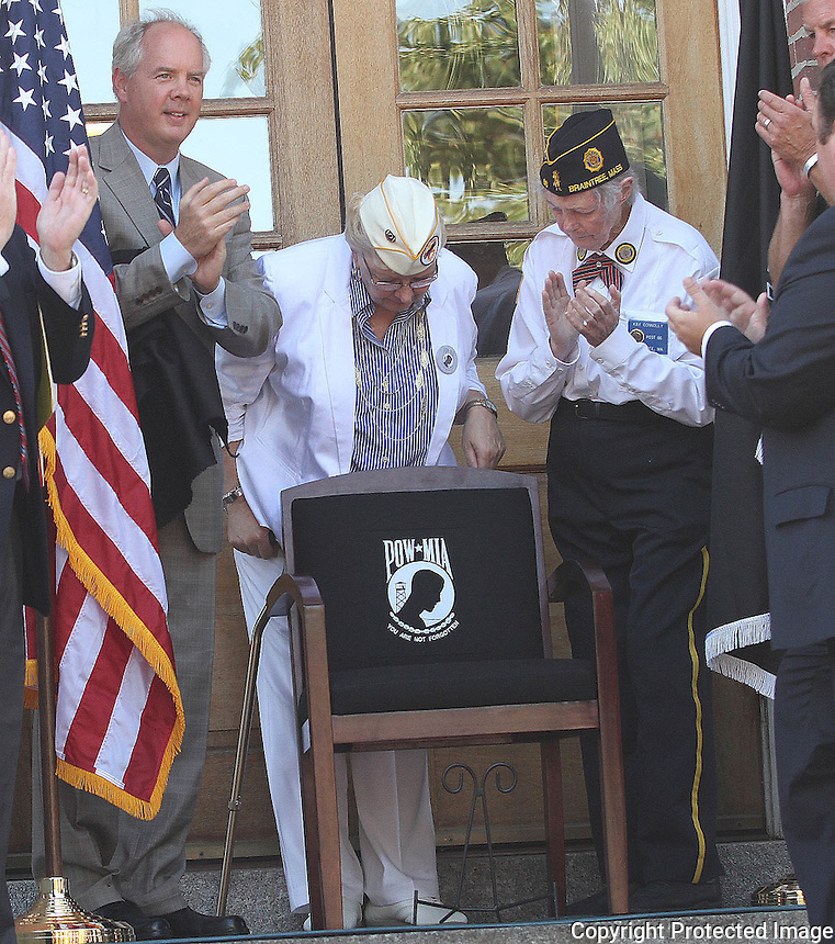 Braintree Mayor Joseph C Sullivan, residence Leona Hoey and Kay Connolly unveil the POW/MIA Chair of Honor during the dedication ceremony at the Braintree Town Hall Sunday September 27, 2014.(Photo by Gary Wilcox)