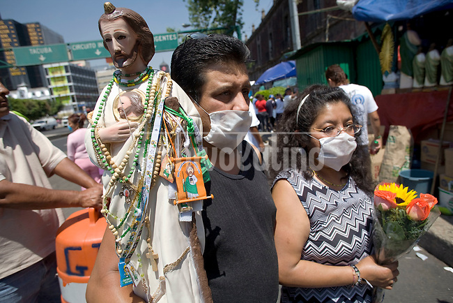 People outside the closed down Judas Tadeo Church  prays  with protective mask to prevent swine flu in Mexico DF. Catholic authorities decided to close all the churches in Mexico DF the epidemic spreading  fast through the country